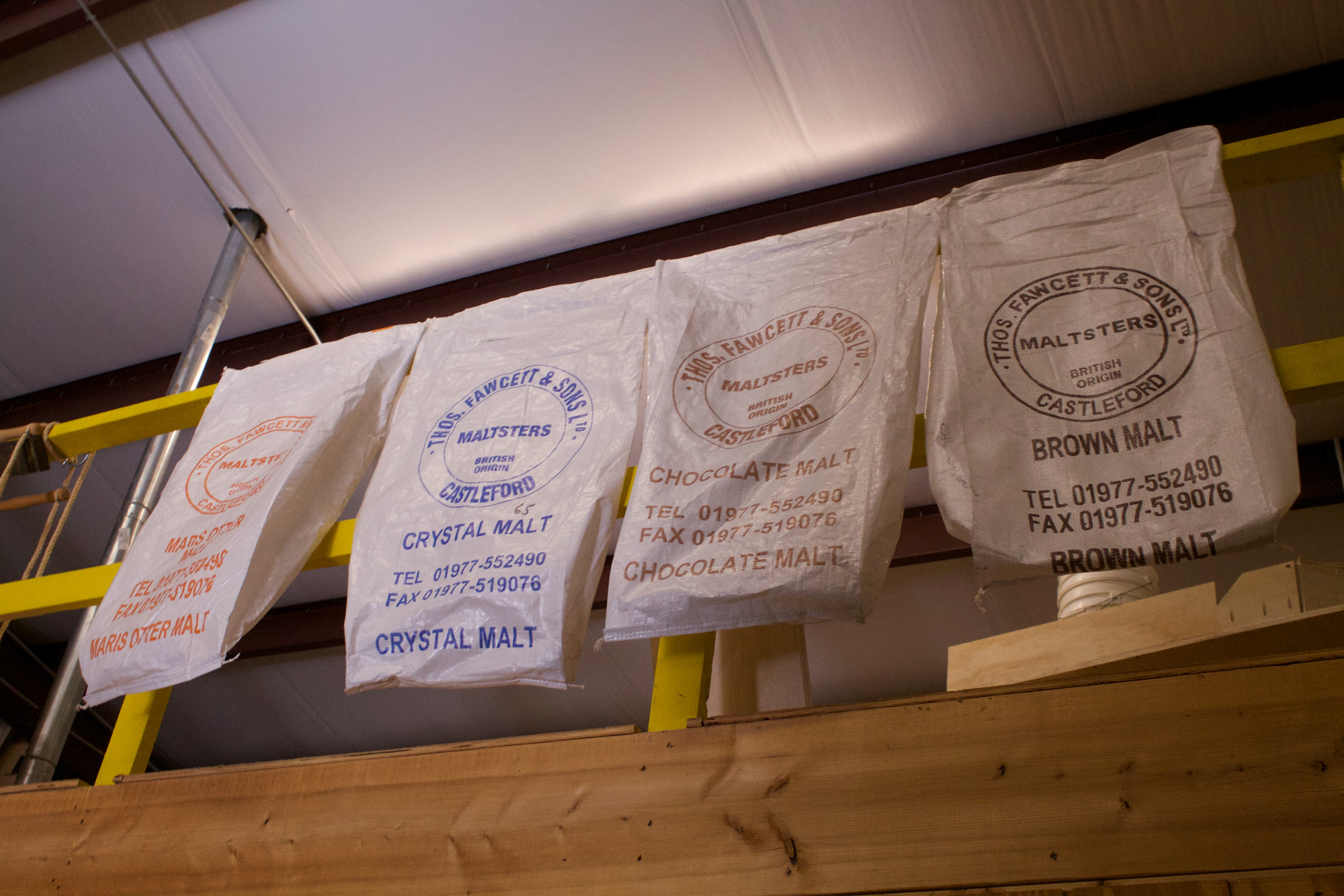 Bags of malts hang from a second story in Rabbit Hole Brewing in Justin,Texas.